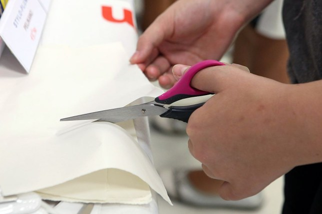 A pair of hands cutting a piece of paper with a left hand on left handers day 2019