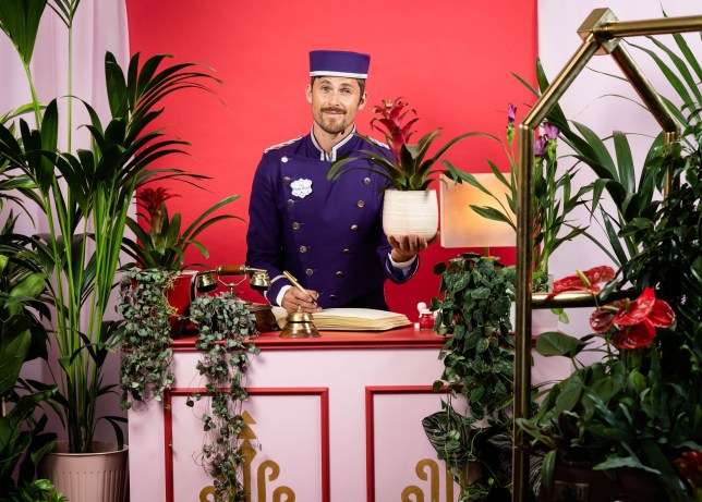 Hotel concierge at plant hotel, holding a plant