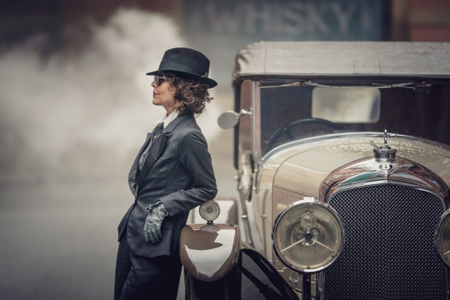 Peaky Blinders Polly Shelby leans against an old fashioned Bentley in a suit