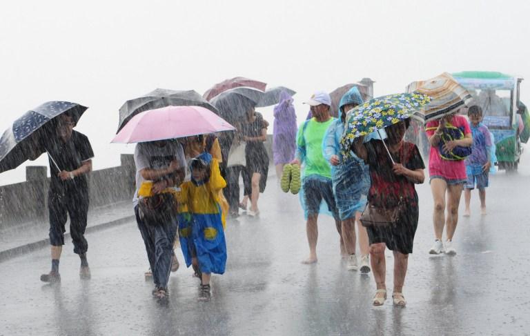 people with umbrellas walk in the rain brought by Typhoon Lekima