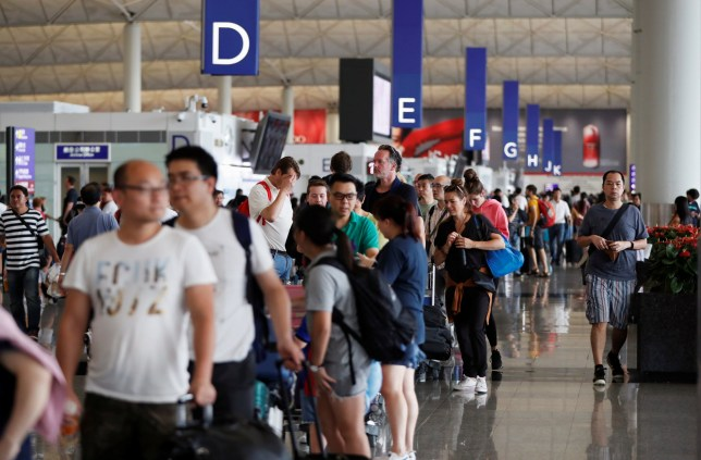 Passengers queue as the airport reopened a day after flights were halted due to a protest, at Hong Kong International Airport, China August 13, 2019. REUTERS/Issei Kato