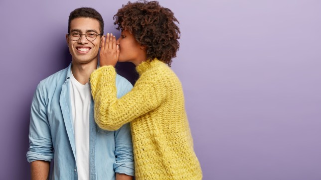 Afro American female whispers secret to boyfriend who has cheerful expression, gossip together, wear casual clothes, stands against purple background with blank space. Diverse couple indoor.; Shutterstock ID 1368595304; Purchase Order: -
