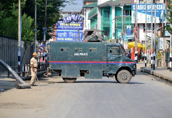 Mandatory Credit: Photo by Saqib Majeed/SOPA Images/REX (10364018i) A policeman stands next an armoured vehicle during the curfew in Srinagar. Strict curfew and a total communication blackout in Kashmir valley following the decision taken by the central government to scrap article 370 which grants special status to Jammu & Kashmir. Curfew in Kashmir, Srinagar, India - 16 Aug 2019