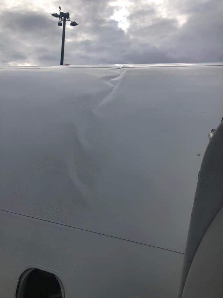 Photo of bent roof of damaged plane