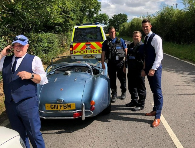 The broken down AC Cobra with the groom posing with police men