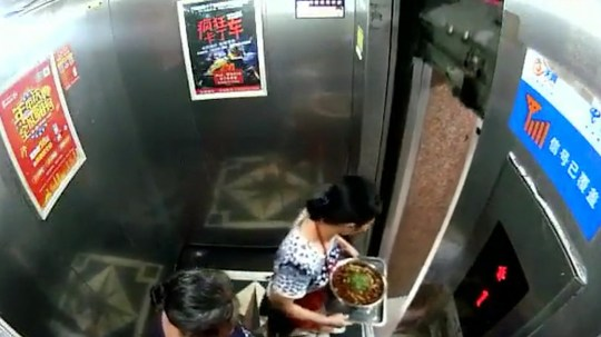 Pic shows: A woman narrowly escapes a faulty lift which rises with the doors fully open. This is the heart-stopping moment a woman narrowly escapes being crushed to death in a faulty lift which suddenly rises as she prepares to step out.