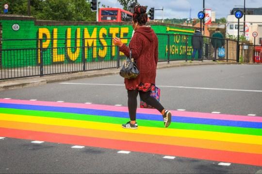 Obowiązkowe źródło: Zdjęcie: Imageplotter / REX (10311332f) Nowy kolor w południowo-wschodnim Londynie. Ludzie przechodzą przez zupełnie nowe przejście tęczowe Pride przy stacji Plumstead, które zostało ukończone dzisiaj na Międzynarodowy Miesiąc Pychy w czerwcu. Kolorowe przejście zostało zainstalowane przez oficjalnych malarzy linii ulicznych za zgodą władz lokalnych i Royal Borough of Greenwich. Przejście uliczne z flagą dumy w Plumstead, Londyn, Wielka Brytania - 15 czerwca 2019