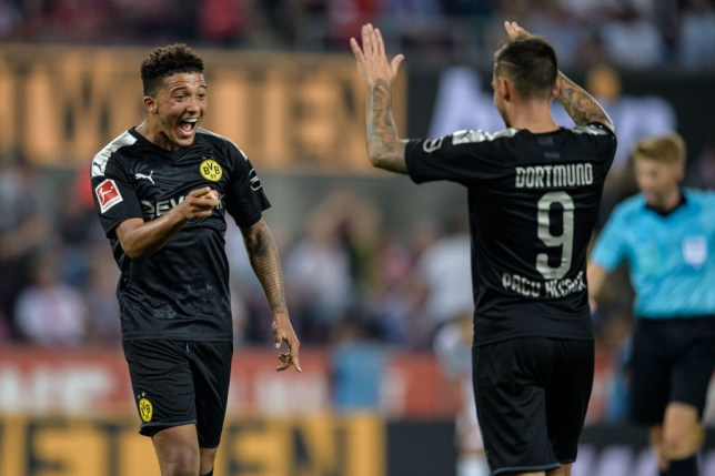 Jadon Sancho celebrates with Paco Alcacer after scoring against FC Koln