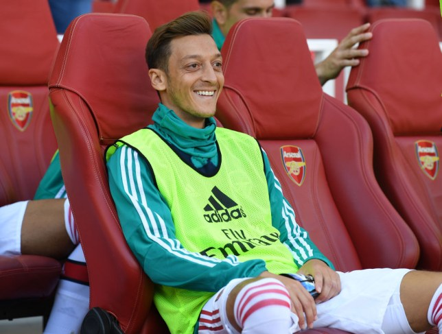 Mesut Ozil smiles on the bench before Arsenal's game against Spurs