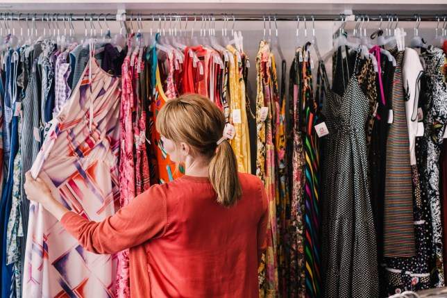 Woman looking through clothing racks in a charity shop