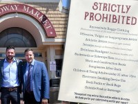 Management standing outside The Choptank seafood restaurant in Baltimore next to picture of their dress code which people have called 'racist'