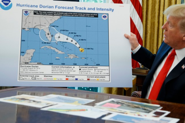 president donald trump holds up a map of hurricane dorian's trajectory which appears to have been doctored with a sharpie