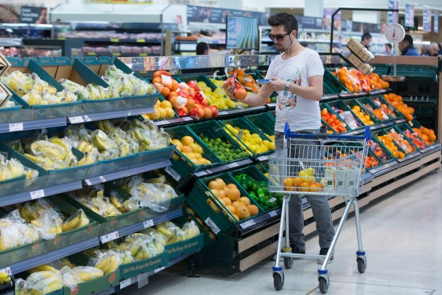 A customer uses a hand-held device to scan a net of oranges as he shops in the fruit and vegetable aisle of a Tesco supermarket