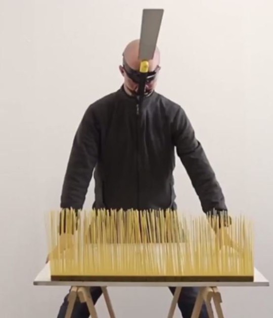 Jan Hakon Erichsen smashing uncooked spaghetti with a hat made of a wooden plank