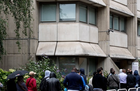 LONDON, ENGLAND - AUGUST 02: People queue around the government Home Office building of Becket House on August 2, 2017 in London, England. Becket House is an Immigration Enforcement Reporting Centre where asylum seekers have to 'sign on' on a regular basis. (Photo by Chris J Ratcliffe/Getty Images)