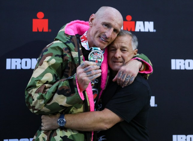 TENBY, WALES - SEPTEMBER 15: Gareth Thomas shows his finishers medal as he celebrates with his partner on completing his first Ironman on September 15, 2019 in Tenby, Wales. (Photo by Huw Fairclough/Getty Images)