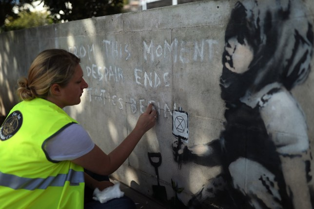Martha Swabey from Fine Art Restoration Company cleaning the artwork before a protective case is placed around the Banksy mural, which appeared following Extinction Rebellion climate change protests on Marble Arch, London, to preserve it for the future. PA Photo. Picture date: Thursday September 19, 2019. Photo credit should read: Yui Mok/PA Wire