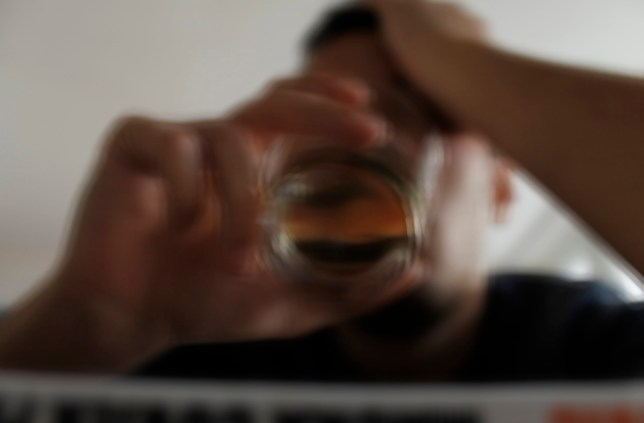 Drunk young adult male with glass of alcohol, studio shot.