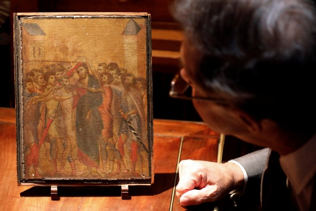 """Art expert Eric Turquin inspects the painting """"Christ Mocked"""", a long-lost masterpiece by Florentine Renaissance artist Cimabue"""