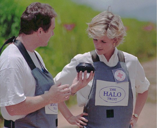 epa07872742 (FILE) - Britain's Princess Diana (R), wearing a heavy duty protection vest and face shield, accompanied by a mine clearing expert of the Halo Trust during her visit to the minefields in the high plateaux near Huambo, Angola, 15 January 1997 (reissued 27 September 2019). Diana's son, Prince Harry, the Duke of Sussex, and his wife Meghan the Duchess of Sussex, are currently on an official visit to Angola. EPA/ANTONIO COTRIM