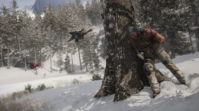 A soldier from Ghost Recon Breakpoint hiding behind a tree injured hiding from military drones
