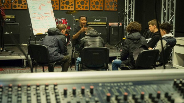 Rapper Ric Flo sat in a studio with a group of young people talking about music