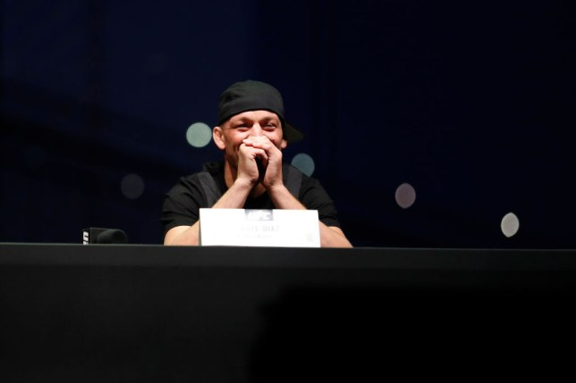 Nate Diaz grins during a press conference with Jorge Masvidal