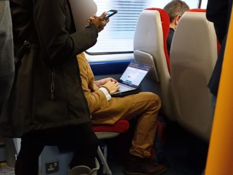 'Selfish' commuter lets woman on crutches stand 'so he can work on his laptop'