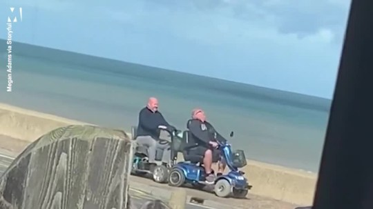 Caption: Old blokes joust on mobility scooters by the beach Picture: Megan Adams via Storyful