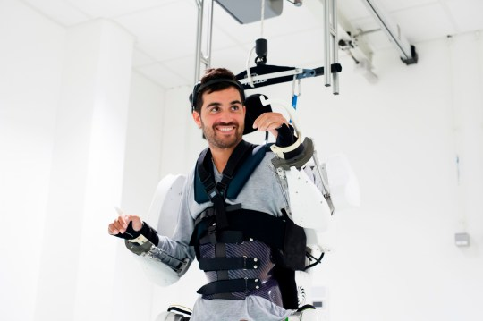 """This handout photograph taken on September 2019 and released by Clinatec Endowment Fund (fonds de dotation Clinatec) on October 3, 2019, shows French tetraplegic 'Thibault' as he stands while wearing an exo-skeleton at Clinatec laboratory at the University of Grenoble. - Paralysed since a fall four years ago, 'Thibault' now manages to direct the movements of an exoskeleton by thought, a kind of motorized armour. A first by French researchers, which opens up important perspectives for paraplegics. (Photo by HO / CLINATEC ENDOWMENT FUND / AFP) / RESTRICTED TO EDITORIAL USE - MANDATORY CREDIT """"AFP PHOTO / FONDS DE DOTATION CLINATEC - CLINATEC ENDOWMENT FUND"""" - NO MARKETING - NO ADVERTISING CAMPAIGNS - DISTRIBUTED AS A SERVICE TO CLIENTS (Photo by HO/CLINATEC ENDOWMENT FUND/AFP via Getty Images)"""