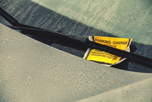 Parking charge ticket under wiper on car on a wet day
