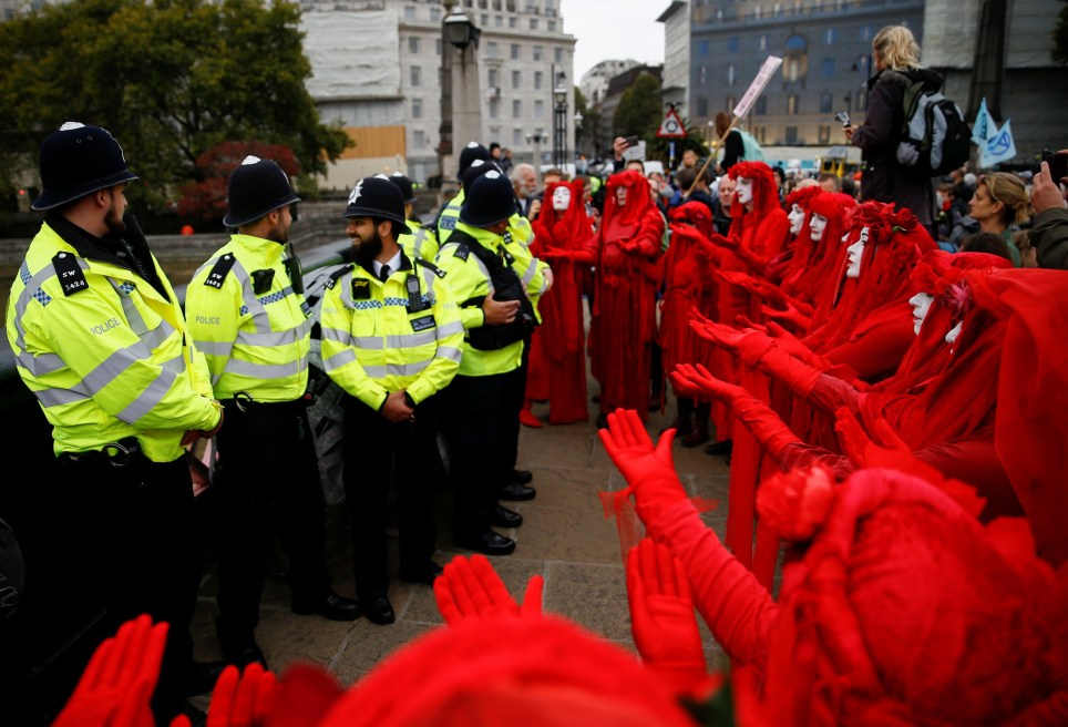 """""""The Red Brigade"""" activists gesture in front of police officers during the Extinction Rebellion protest in London, Britain October 7, 2019. REUTERS/Henry Nicholls"""