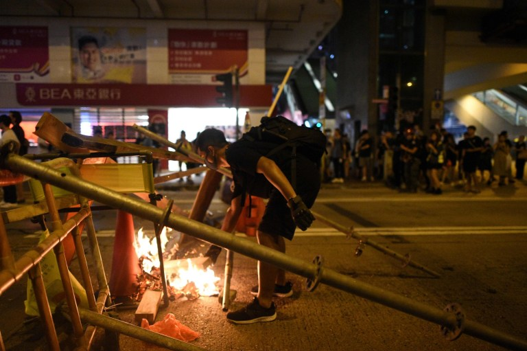 This photo taken on October 7, 2019 shows a protester setting fire to a barricade in the street during a stand off with police near the Mongkok police station in Hong Kong. - Semi-autonomous Hong Kong has been battered by four months of increasingly violent pro-democracy protests sparked by opposition to a now-scrapped bill allowing extraditions to China. (Photo by Mohd RASFAN / AFP) (Photo by MOHD RASFAN/AFP via Getty Images)