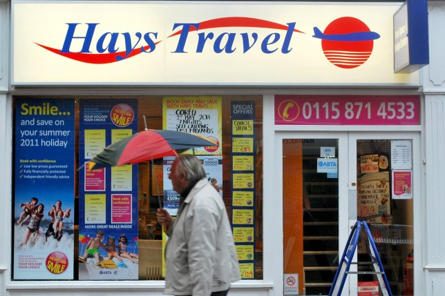 A man shelters from the rain underneath a broken umbrella as he walks past a Hays Travel shop