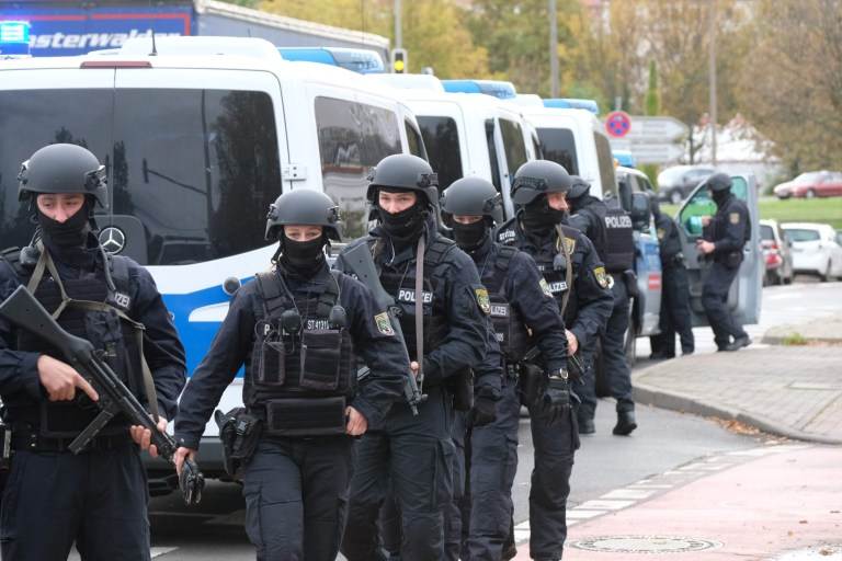 """Policemen walk through a street close to the site of a shooting in Halle an der Saale, eastern Germany, on October 9, 2019. - At least two people were killed in a shooting on a street in the German city of Halle, police said, adding that the perpetrators were on the run. """"Early indications show that two people were killed in Halle. Several shots were fired. The suspected perpetrators fled in a car,"""" said police on Twitter, urging residents in the area to stay indoors. (Photo by Sebastian Willnow / dpa / AFP) / Germany OUT (Photo by SEBASTIAN WILLNOW/dpa/AFP via Getty Images)"""