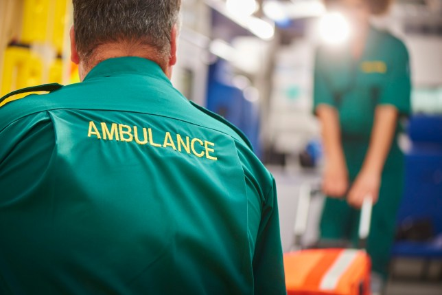 two uk ambulance staff members pull a stretcher on or off of their ambulance . We are looking over the shoulder of the male paramedic focussing on the word ambulance on his back.They are wearing a green ambulance uniform typical of uk paramedics. The female paramedic and the back of the ambulance are defocussed .