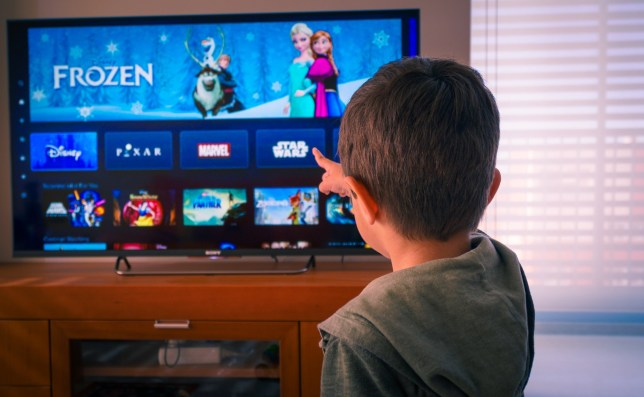 A little boy watches Disney films