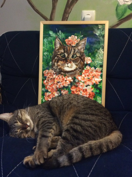 Cat next to floral painting of itself