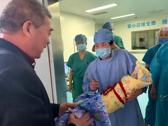 La foto muestra: una partera le entrega al Sr. Huang, de 68 años, su hija recién nacida; Según los informes, una mujer de 67 años se convirtió en la nueva madre más vieja de China después de dar a luz a una niña que, según ella y su esposo, también fue concebida naturalmente.