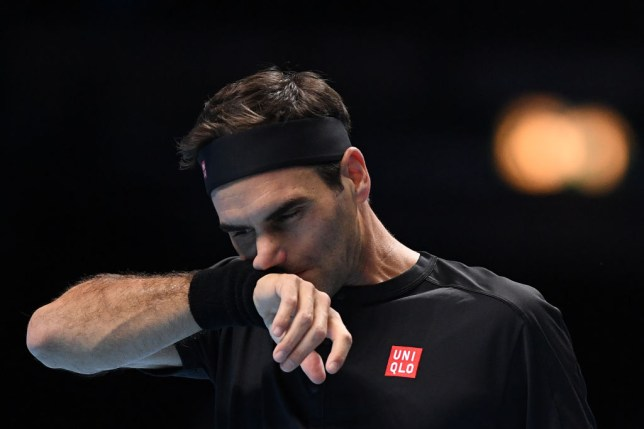 Roger Federer wipes sweat from his face during his ATP Finals defeat to Stefanos Tsitsipas
