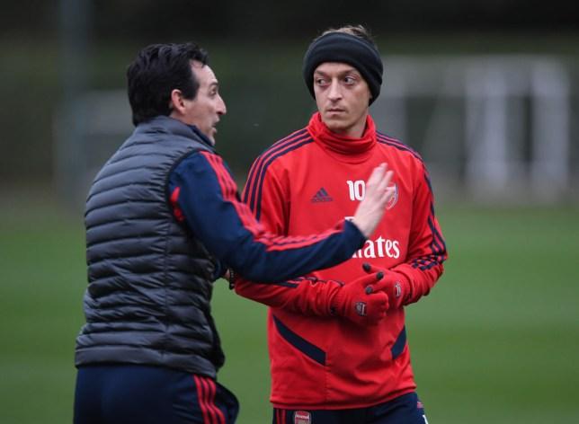 Unai Emery gives instructions to Mesut Ozil during training