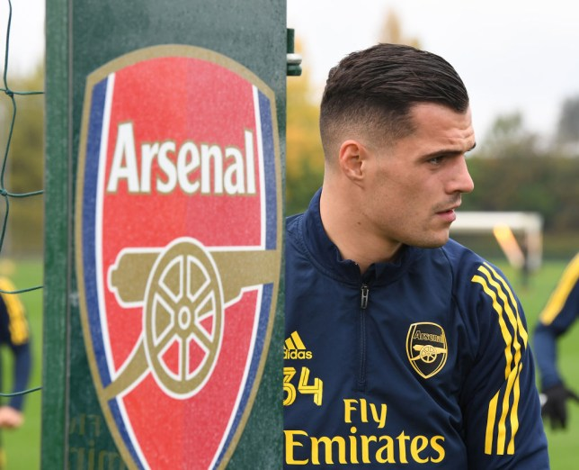 Granit Xhaka looks on during training standing beside the Arsenal crest