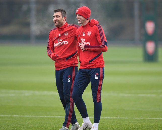 Sokratis and Rob Holding laugh together during an Arsenal training session