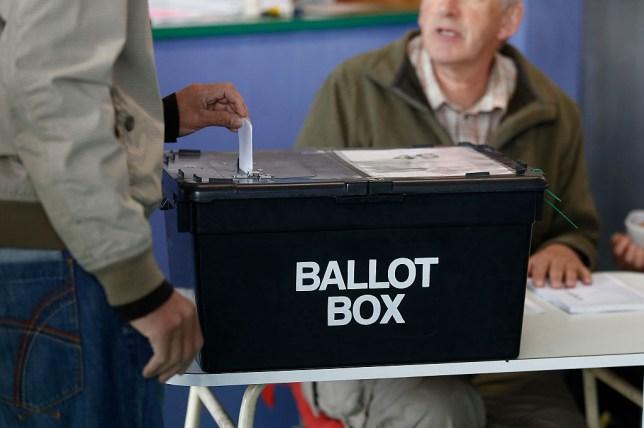 a person casting their vote in a ballot box