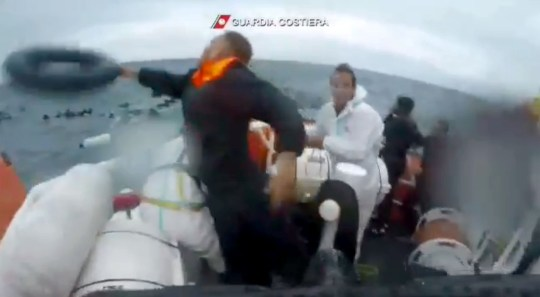 """This photo grabbed from a video taken on November 23, 2019 and handout by the Italian Coast Guards (Guardia Costiera) on November 25, 2019 shows a rescuer throwing a buoy to migrants into the sea off the island of Lampedusa, after they fell from a ten-metre boat. - Italian coast guards on November 23, 2019 said they had rescued 143 migrants off the island of Lampedusa although around 20 others were apparently missing according to the survivors. (Photo by Handout / GUARDIA COSTIERA / AFP) / RESTRICTED TO EDITORIAL USE - MANDATORY CREDIT """"AFP PHOTO /GUARDIA COSTIERA"""" - NO MARKETING NO ADVERTISING CAMPAIGNS - DISTRIBUTED AS A SERVICE TO CLIENTS --- (Photo by HANDOUT/GUARDIA COSTIERA/AFP via Getty Images)"""