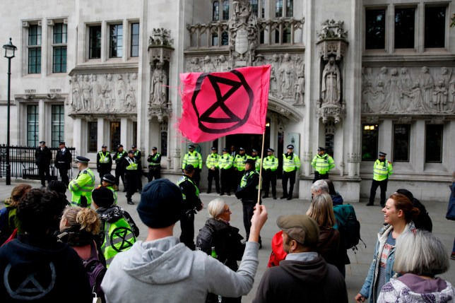 Climate activists protest outside the Supreme Court, during the eleventh day of demonstrations by the climate change action group Extinction Rebellion, in London, on October 17, 2019. - Activists from the environmental campaign group Extinction Rebellion have vowed to challenge a blanket protest ban imposed by the London police. (Photo by Tolga AKMEN / AFP) (Photo by TOLGA AKMEN/AFP via Getty Images)