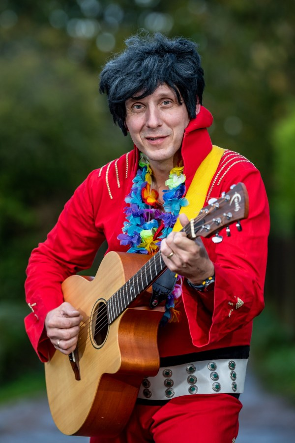 """Elvis impersonator Simon Goldsmith, 46 outside his home in Little Bealings, Suffolk. See SWNS Cambridge copy SWCAelvis: One of Britain's worst Elvis Presley impersonator was snubbed by a tribute competition organiser who said he was """"too rubbish"""" to take part. By day, Simon Goldsmith is your friendly neighbourhood postie- but by night he transforms into the King of Rock n Roll himself by putting on his sequin-clad white suit. And while he admits, his act is """"low budget"""" and a """"bit rubbish"""" he said always puts on a good show and doesn't take himself too seriously."""