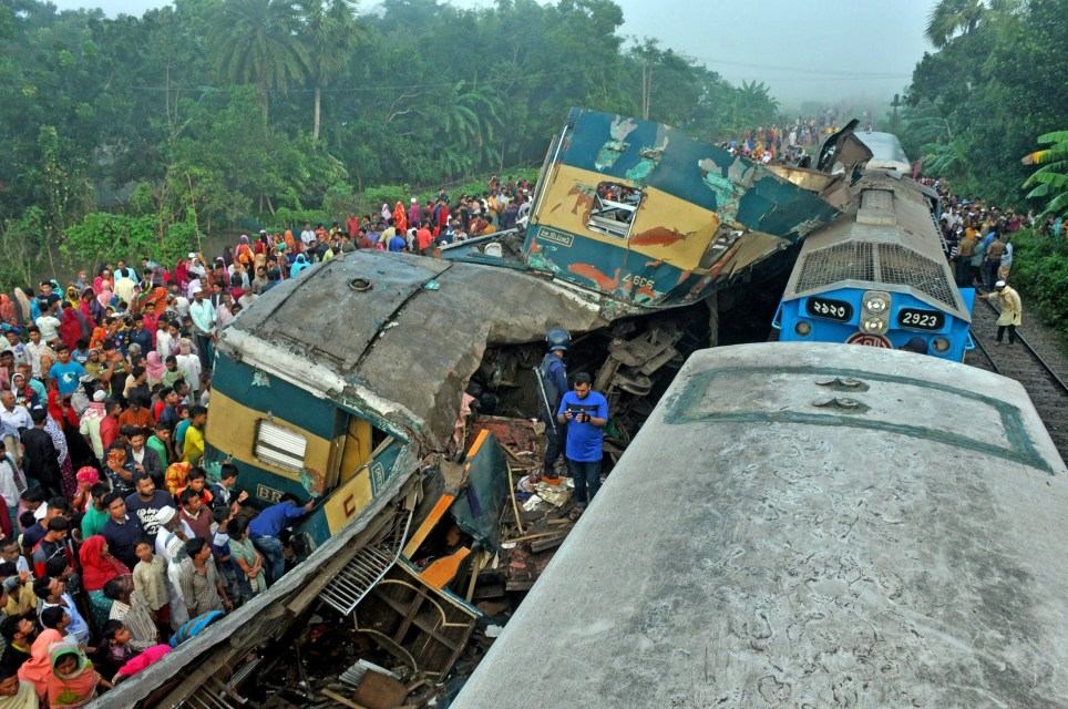 epa07989914 Rescue workers and people gather beside the remains of a damage passenger train in Kasba Upazila, Brahmanba district, Bangladesh, 12 November 2019. According local media reports, at least 16 people were killed and 100 others injured after two trains as two trains heading in opposite direction on the same track collided. EPA/STR