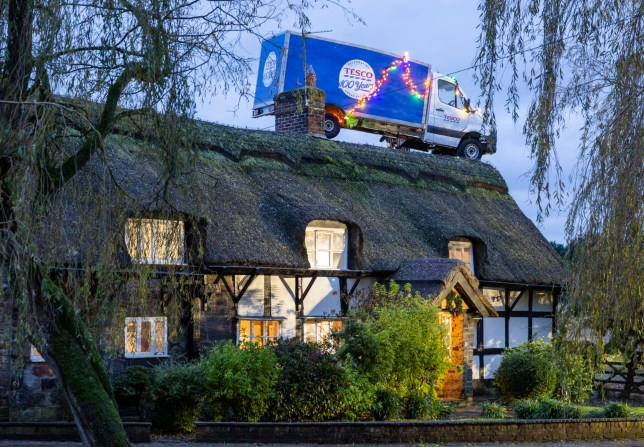 "This is the bizarre moment a delivery van was spotted ???parked??? on top of a thatched cottage in Knutsford, Manchester, - like Santa???s sleigh! See SWNS story SWBRvan. A supermarket delivery van appears to have gone above and beyond on its rounds - by ending up 'parked' on a customer???s roof. The wayward van came bearing goodies - like Santa???s sleigh without the reindeer - in the form of the weekly shop. The van, which is said to hint at Tesco's new Christmas ad, was also given a festive touch, decorated with hundreds of multicoloured festive lights.The sight attracted a crowd of locals from the small community of Knutsford, Manchester, who came to ???check out??? the surprising scene.There was speculation as to whether a ???Supermarket Santa??? had arranged a delivery straight down the chimney, though the Tesco delivery driver was nowhere to be seen. Knutsford resident Jewel, 29, said: ???It???s unbelievable! I???ve never seen anything quite like this, especially around here. ""It really feels like something out of a Christmas movie.???"