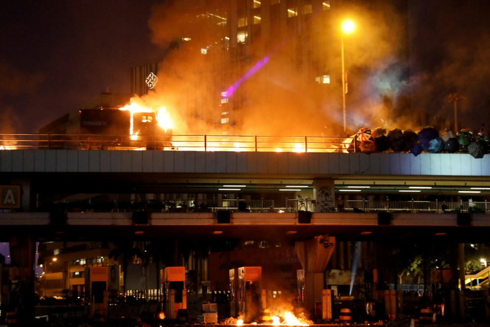 Police armoured truck burns as it was hit with Molotov cocktails, after an attempt to ram the barricade at a bridge above the entrance to the Cross Harbour Tunnel during clashes outside Hong Kong Polytechnic University (PolyU) in Hong Kong, China November 17, 2019. REUTERS/Adnan Abidi